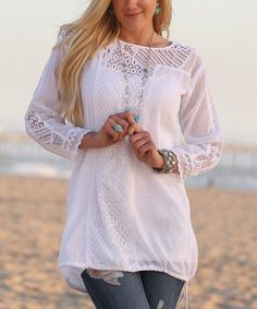 Add a vintage-inspired touch to your ensembles with this elegant tunic that features a drawstring at its hem and sweet crochet accents along its sleeves and bodice.