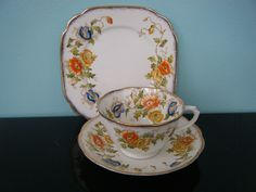 ROYAL ALBERT CROWN CHINA TRIO WITH BLUE,ORANGE AND YELLOW FLOWERS