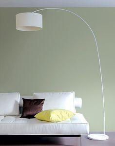 Un mur vert amande et une déco épurée pour un salon résolument contemporain.