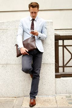 .A classic look with a pale blue blazer, grey slacks, brown tie and shoes and bag. Very well-assembled.