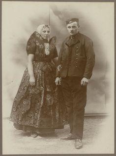 Man en vrouw in Axelse streekdracht. Beide zijn gekleed in hun zondagse kleding. De opname is gemaakt in 1913 te Amsterdam, tijdens het Klederdrachtenfeest. Dit was onderdeel van de festiviteiten rond de 100-jarige onafhankelijkheid van Nederland (1813-1913). #Axel