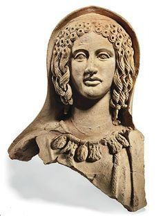 AN ETRUSCAN TERRACOTTA VOTIVE FEMALE BUST   CIRCA 3RD-2ND CENTURY B.C.   With lidded articulated eyes and elaborately coiffed hair, centre- parted and falling into ringlets on either side, wearing large inverted pyramidal earrings and a necklace of large pendants decorated with relief figures of various heroes and deities, a mantle pulled up over the back of her head, preserving traces of red, pink and yellow pigment