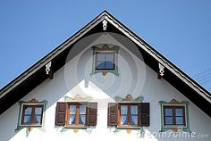 Photo made in Oberammergau in Bavaria (Germany). The picture shows the upper part of the facade of one of the typical houses of the country where almost all the houses are painted and some with scenes depicting fairy tales. Image sivedono five windows, two with dark green and white curtains, dark three without two of which no curtains.