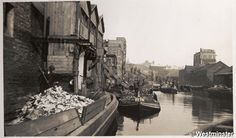 """Caption: """"Black and white photograph of refuse being loaded onto barges and being transported along the Grand Union Canal by Paddington Borough Council and St Marylebone Borough Council"""""""