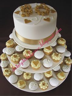 Well, this is a little bit more what I am thinking. A small cake over many cupcakes...all gold and Ivory. Not crazy about the cake on top.