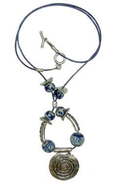 Collar de cuero azul de 2mm, decorado con entrepiezas metálicas de tubo curvadas con relieve, bolas de cerámica en azul y blanco decoradas en dos tamaños y rematado con colgante redondo con forma de espiral de 40x44mm color plata vieja.