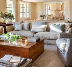 Salón con sofá en blanco roto y mesa de centro de madera maciza tipo bahúl