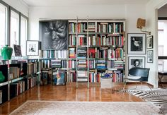 Great and colorful bookshelf in the living room with books about art and design.