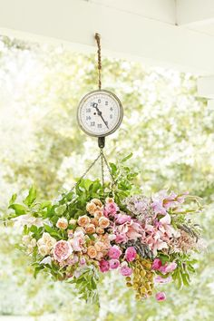 """Hanging Scale:  An old hanging scale can handle a load of blooms and makes for a clever, porch-friendly alternative to a hanging basket. """"Old scales were made for food, so I mixed in apple branches and dates with a burst of dahlias, roses, and gladiolus,"""" Kiana says."""