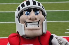 The Scarlet Knight is as well-known as some of the best Rutgers athletes, yet his true identity remains anonymous to most.    The university's mascot for more than a half-century, the Scarlet Knight took over from the rooster Chanticleer in 1955. The Knight has undergone several metamorphoses in his cheerleading career: as a real person on horseback, a short-lived mechanical horse and rider, and now as the diminutive, but challenging, figure with a big head and an oversized sword.