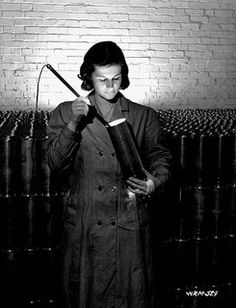 Female munitions worker uses light to inspect interior of 25-pounder field gun case at a munitions plant (prob. Robert Mitchell Co.)  / Dans une fabrique de munitions, une ouvrière utilise une lampe pour examiner l'intérieur d'une douille d'obus pour cano by BiblioArchives / LibraryArchives, via Flickr