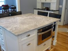 Modern White Stained Wooden Island Built In Microwafe Cupboard Using Square Light  Gray Quartz Countertop,