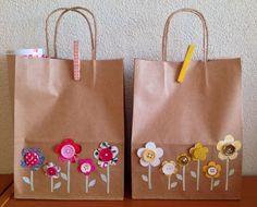 Bruine papieren draagtas/kadotas versierd met bloemen die gemaakt zijn met knopen, stukjes behang, papier en oude tijdschriften. Knijpers zijn beplakt met washi tape.