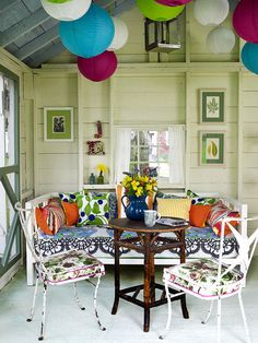 Sunroom inspiration: A collection of mismatched furniture and colorful accessories look right at home in this casual sunporch. The various patterns blend well with one another because theyre all relatively similar in scale. Circular lanterns hanging from the ceiling tie in with the color palette and provide ambient lighting when the sun goes down. | Better Homes & Gardens