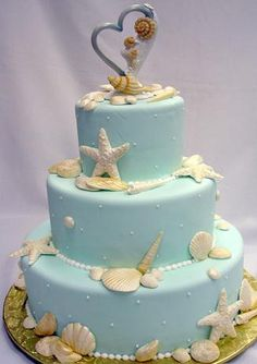 Tiered wedding cake with pale blue frosting and sea shell accents! - #beachweddingcake #weddingcake