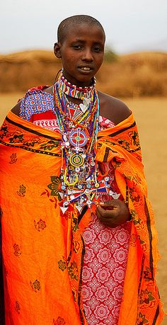˚Maasai woman, at the square of her village, in Amboseli. Masai women typically wear vast plate-like bead necklaces, and colourful wraps called kanga.