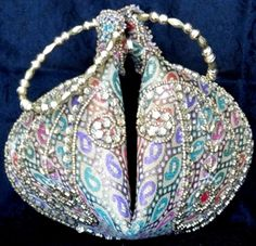 his very elegant handmade evening clutch purse is shaped like a 'potli bag'. It is made of brocade cloth and has golden bead work on it. It closes with a zip and also has a magnetic button to make it fold in. Bangle shaped golden handles enhance its beauty even more. A beautiful evening accessory, can be worn like a bangle on the wrist. - See more at: http://giftpiper.com/Brocade--Beadwork-Potli-Bag-Multicolored-Paisley-id-523427.html#sthash.ICa6xNg3.dpuf