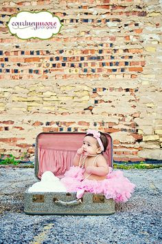 6 month old session...with the blue suit cases in front of the pink garage door