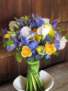 Yellow roses, white lisianthus, blue delphinium and irises, accented with green bulplurum.