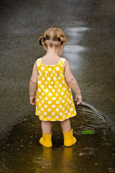 Bright Yellow polka dot dress with cute yellow boots..mesmerized by a pond of water..
