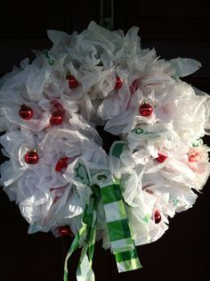Christmas Wreath made out of  shopping bags with red and green printing on it. They are on a wired coat hanger. Used small red ornaments on it as well. Great easy recycling project for the kids.