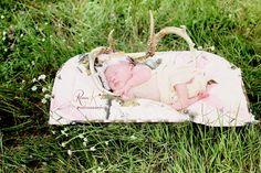 newborn baby girl with deer horns in the field