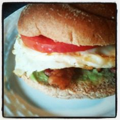 egg sandwich on a whole wheat bun with avocado, sliced tomato, bacon ...
