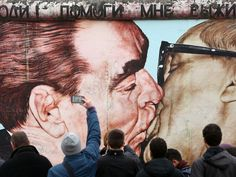 "Visitors photograph graffiti by Dmitri Vrubel of Russian Leonid Brezhnev and German Erich Honecker kissing under the words, in Russian, ""Pomogi mne vyzhit' sredi etoy smertnoy lyubvi,"" or ""My God, Help Me to Survive This Deadly Love,"" based on a photograph by Regis Bossu in East Berlin from Oct. 7, 1979. Berlin is commemorating the 25th anniversary of the fall of the Berlin Wall."