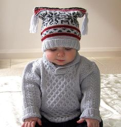 This fabulous little baby jumper has a very simple cable pattern, matching boots and jester style hat with a Nordic feel fair isle pattern - find the pattern on LoveKnitting!