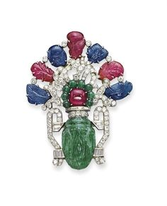 AN ART DECO EMERALD, SAPPHIRE AND RUBY DOUBLE-CLIP BROOCH -  Of 'giardinetto' design, set with a series of carved sapphire and ruby leaves, with brilliant-cut diamond vines, the centre set with a ruby cabochon and emerald bead flowerhead, in an earlier carved Moghul emerald vase with diamond-set handles, mounted in platinum, circa 1930