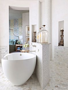 Raising a half wall in the bath's center gives some privacy to the contemporary tub, conceals plumbing pipes, and acts as a display shelf. The sculptural divider, which mimics other curved surfaces in the bath, stands out because of its striking silhouette, mosaic-tile finish, and architectural fittings.