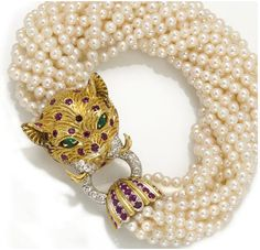 A cultured pearl, ruby, emerald and diamond torsade bracelet with leopard-head terminal; composed of sixteen strands of cultured pearls; mounted in twenty-two karat bicolor gold; length: 7 1/2in. (one ruby deficient)