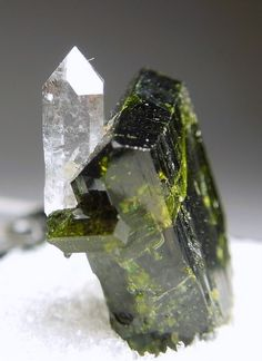 Epidote Quartz  Sulzer Alaska USA  A tabular, dark green Epidote crystal, with a little, terminated Quartz crystal perched on the side. The Quartz is gemmy and both minerals are lustrous. From Alaska. Ex. Foerster Collection.