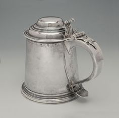 An Early American Silver Tankard - Maker: Philip Syng, Philadelphia, PA - c.1750 - 7''(H) 31 oz. 8 dwt. Tapered cylindrical with domed cover on molded foot. Engraved on handle M over W*H and on front RH in script.