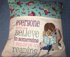 Unicorn reading cushion, with the words Everyone should believe in something I believe in Reading blue unicorn fabric Pocket has an embroidered design that can hold a book Measures approx 15X15 inches Please note the fabric used for the book may be different to that pictured  Postage