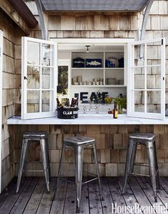 Outdoor Counter  Designer Erin Martin extended the honed Calacatta marble counter from the kitchen of this California beach house outside to make passing food easier. Tolix Marais stools from Design Within Reach are pulled up to the counter.