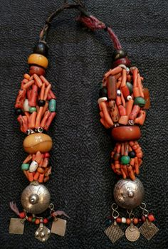 BERBER HEAD ORNAMENT    A pair of Berber amulets, worn as a woman's head ornament     Silver, coral, turquoise, amber, carnelian and assorted glass beads, length 29cm   Morocco, 19th century