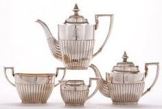 AN IMPRESSIVE FABERGÉ SILVER FOUR-PIECE TEA AND COFFEE SERVICE, MOSCOW, CIRCA 1910. Comprising a coffee pot, a teapot, a two-handled sugar bowl and creamer, the lower sections of the bodies gadrooned and set on reeded foot rims, the lids hinged, with harp-shaped handles and gilded interiors, engraved with Cyrillic initials AS. Hallmarked Moscow 1908-1917, and in Cyrillic KFABERGE beneath the Imperial Warrant, and with 84 silver standard, and defaced inventory number 22929.