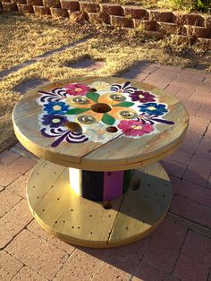 """Mexican flowers hand painted cable   """"spools"""" table for outside."""