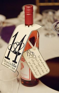 "Wine bottle table numbers and tag with toast poem. ""This wine will serve as the toast tonight so share with your table and raise your glass with delight!"""