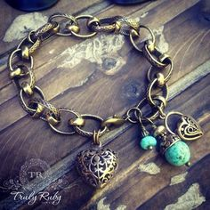 Bronze ornate chain with a bronze filigree heart and Turquoise gems with bronze charms and beads.