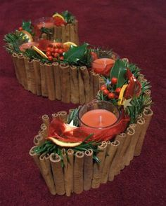 cinnamon scented candles, spruce from the tree, orange slices, red ribbon and holly, sprinkled with a few gold stars. The spruce and holly is arranged in oasis so it will last well over Christmas.: