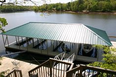 Wahoo community 4-slip aluminum floating boat dock with corrugated metal hip roof. Dock connected to deck by flat gangway with aluminum rails.