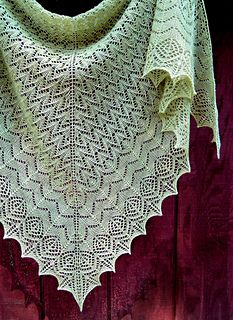 Edwina is a delicate, top-down triangular lace shawl with traditional and Estonian stitch patterns that flow seamlessly from one to the next until ending in a geometric border that echoes the shapes created by the patterns of the shawl body.