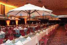 Outdoor umbrellas add a fun atmosphere to an indoor event. Blue, green and white tablescape with gold lanterns Outdoor Umbrellas, Gold Lanterns, Moroccan Theme, Centerpieces, Table Decorations, Party Stuff, Patio Design, Event Decor, Event Planning