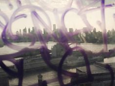 CHRISTOPHER ANDERSON, NYC, View of Manhattan and the Brooklyn Navy Yards through a window covered in graffiti, 2011