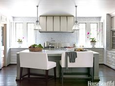 I like the hood... Lee's Dual Seat Counter Benches at the kitchen island accommodate the four children of a family in an Alabama house designed by Paige Schnell and Doug Davis. Tiles are Akdo's Mini Brick. Urban Archaeology pendant light. JONNY VALIANT  - HouseBeautiful.com