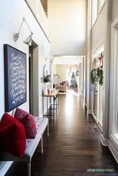 Christmas entryway hallway with linen bench, red plaid pillows, wreaths, swing-arm sconces and 'Doxology' canvas artwork. #christmasdecor #christmasstyle #holidaydecor