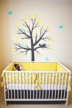 Adorable yellow gender neutral nursery with tree wall mural