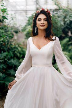 Prosta suknia ślubna z długim rękawem z kolekcji 2020 r. pracowni sukien ślubnych i wieczorowych DAMA Couture, w kolorze ecru (mleczno biała). Jest to elegancka i minimalistyczna suknia ślubna z dekoltem, uszyta z jedwabnego szyfonu (podobnej do muślinu). Sukienka jest gładka i zwiewna, o kroju prostych sukien ślubnych bez tiulu czy gipury. Posiada rozcięcie na nogę. Jest skromna, ale może być uszyta z trenem. Możliwe są także kroje sukienek plus size. #sukniaslubna #prostasukniaslubna Boho Wedding, Wedding Gowns, Wedding Aisle Outdoor, Temple Dress, Civil Wedding, I Dress, Bridal Style, Bridal Dresses, Diana